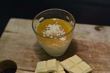 Panna cotta van witte chocolade afgewerkt met coulis van mango ( trendy glas inbegrepen)